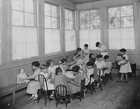 Black and white photograph of girls with dolls at the Emanuel Cohen Center in Minneapolis c.1925.