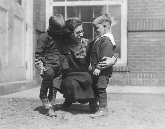 Black and white photograph of a woman with two boys at the Northeast Neighborhood House, c.1925.