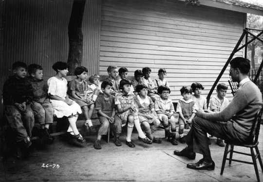 Black and white photograph of a man telling a story to residents of the Jewish Sheltering Home for Children in Minneapolis, c.1925.
