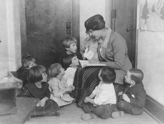 Black and white photograph of a woman reading to children at the Neighborhood House, c.1925.
