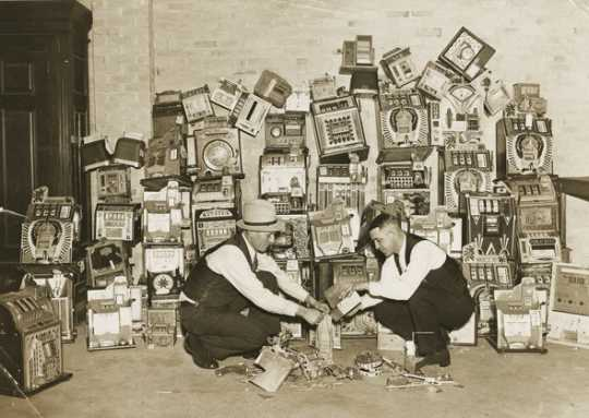Black and white photograph of a police raid on slot machines, St. Paul, 1935. Photograph from the St. Paul Daily News.