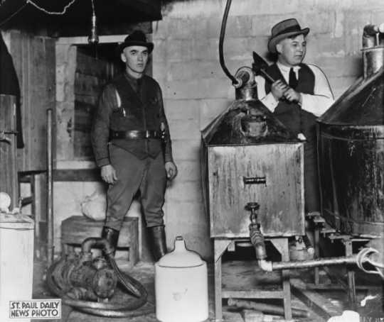 Black and white photograph of police destroying an illegal alcohol still during Prohibition, 1925. Photographed by the St. Paul Daily News.
