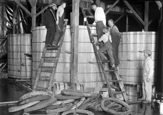 Black and white photograph of a group of people dismantling a still at Pillsbury and Charles Streets in St. Paul, c.1925.