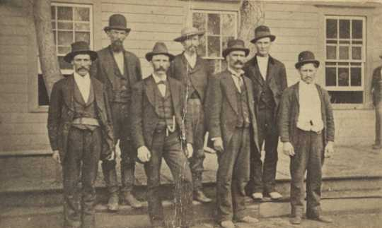 "Black and white photograph of the six officials and volunteers, known as the ""Madelia Seven,"" who captured the Younger brothers outside Madelia on September 21, 1876."