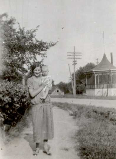 Black and white photograph of a woman and baby posing in front of the band shell in Hanover, ca. 1925–1930.