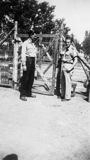 Black and white photograph of Harvey Fleshner with a Peterson farm employee outside the gates of the German prisoner of war camp, ca. 1943–1945.  Used with the permission of the Historical and Cultural Society of Clay County.