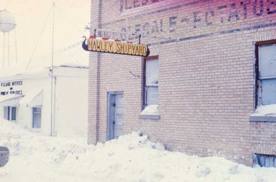Color image of the Hawley Shipyard sign on the old warehouse that was used to build and store the Hjemkomst. From the Tom Asp Collection, Historical and Cultural Society of Clay County.