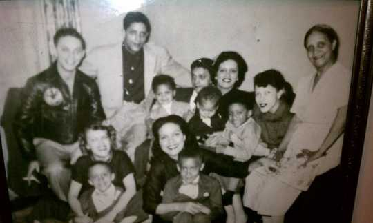 Black and white photograph of Hilda Simms surrounded by her mother, several of her siblings, and nephews, c.1955.