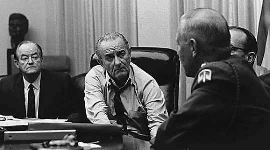 Black and white photograph of Vice President Humphrey discussing the Vietnam War with President Johnson and military officials, c.1965.