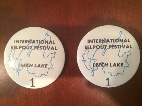 """Buttons issued the first year of the International Eelpout Festival, 1980. The buttons were numbered, but four buttons featured the number """"1"""" for Don and Debbie Overcash, Ken Bresley, and Barbara Robers. From the private collection of Don Overcash, used with permission."""