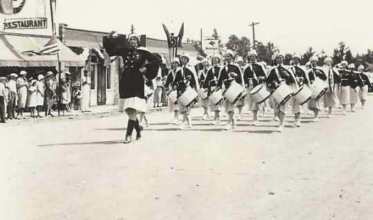 Black and white photograph of the American Legion Auxiliary drum and bugle corps on parade in Bagley, Minnesota, 1935.