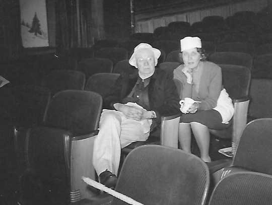Black and white photograph of Charles and Louise Hiller sitting in theater seats, ca. 1940s.