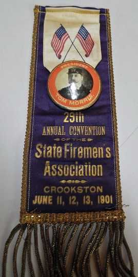 Color image of a badge worn by Fire Chief Tom Morris at the Firemen's Convention held at Crookston city hall, 1901.