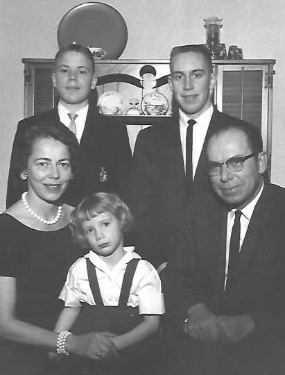 Black and white photograph of Ernotte and Ardis Hiller (seated), holding Mary Hiller; in the back are Chuck Hiller (right) and Jeff Hiller (left), 1961.