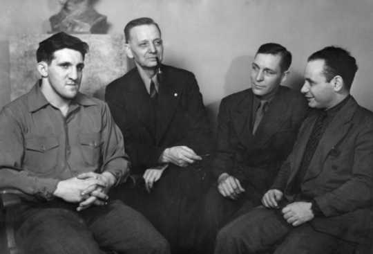 Black and white photograph of Jake Cooper, Oscar Coover, Harry DeBoer, and Max Geldman at the Minneapolis Headquarters during the time of their trial, 1941.