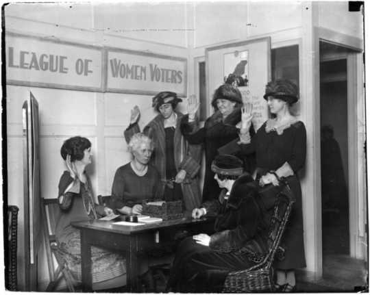 League of Women Voters swearing in new members or registering women to vote, ca. 1923.
