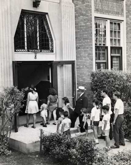 Black and white photograph of adults and children walk through the entrance of the J. E. C., c.1940.