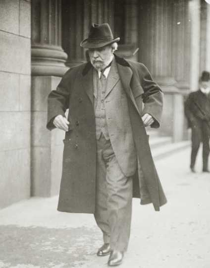 Black and white photograph of James J. Hill walking down street with overcoat flapping, c.1915.