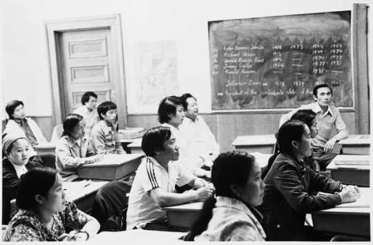 Black and white photograph of Hmong students in a class at the Lao Family Community Center inside a branch of the St. Paul YMCA, c.1980.