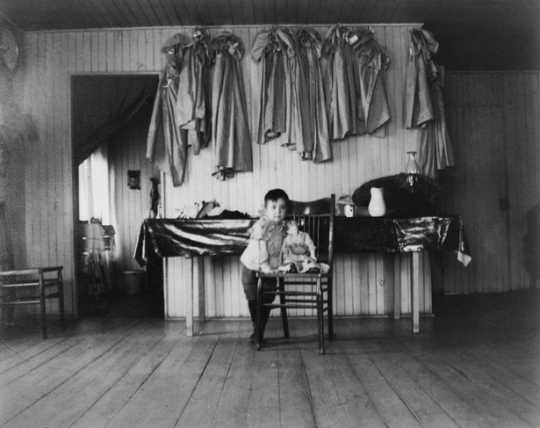 Black and white photograph of a young child inside a Native American boarding school, c.1890s.
