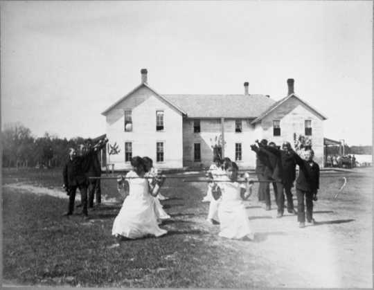 Black and white photograph of students performing a drill on the grounds of a Native American boarding school, c.1890s.