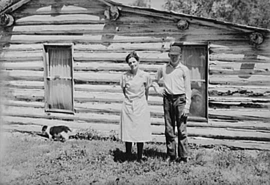 Black and white photograph of Mrs. Cornelius and son standing by their log house, homesteaded in 1912.