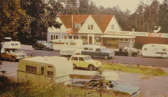 Color image of Lamb's Resort, ca. 1968, after Skip and Linda Lamb purchased it; a new laundry and grocery addition is at the right of the inn.