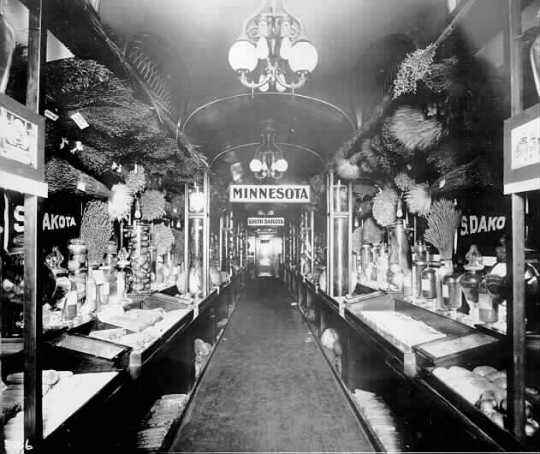 Black and white photograph of a Minnesota exhibit of farm product in railway car, Great Northern Railway, Western Governors Special, ca. 1911.