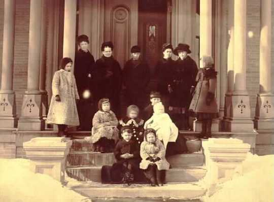 Black and white photograph of Mary Mehegan Hill, Grace Upham, and several of their children at the Uphams' Lowertown St. Paul home, c.1883.