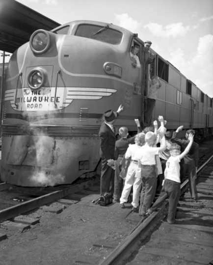 Black and white photograph of agroup of kids visiting a Milwaukee Road locomotive. Photograph by the Star Tribune Company, April 4, 1948.