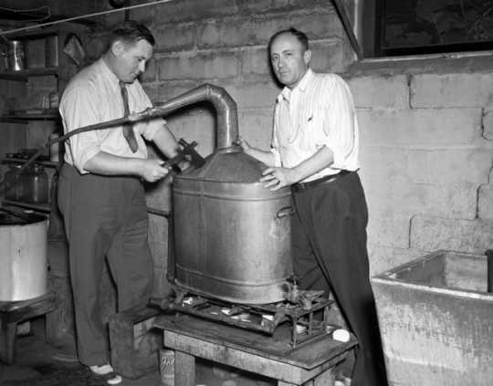 Black and white photograph of two men breaking apart an illegal still,1940. Photographed by the Minneapolis Star Tribune.