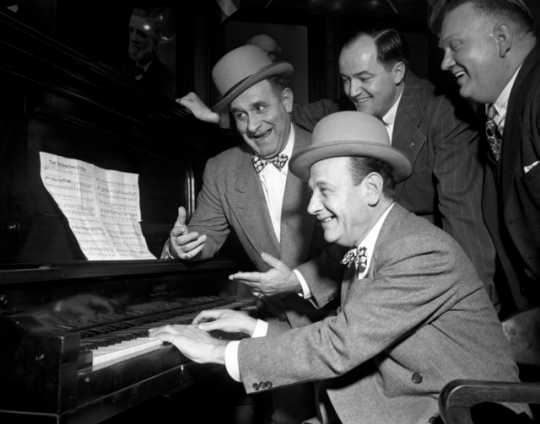 Black and white photograph of Jimmy Durante (back left) and Mayor Hubert H. Humphrey sing along with two unidentified men, 1946.
