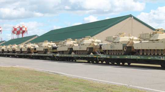 Color image of M1 Abrams tanks arrive at Camp Ripley on flatcars, 2015.