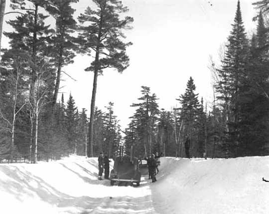 People standing around a car on the Gunflint Trail during winter. Photograph by Kenneth Melvin Wright, ca. 1944.