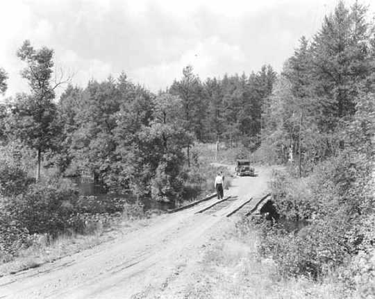 Car approaching a bridge with pedestrians along the Gunflint Trail. Photograph by William F. Roleff, 1936.