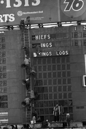 Black and white photograph of Viking fans strip the scoreboard after the Vikings lose to Kansas City in the last game played at Met Stadium, 1981. Photograph: John Doman, St. Paul Dispatch & Pioneer Press.