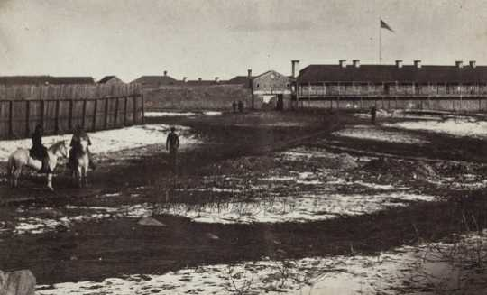Black and white photograph the south side of Fort Snelling showing the gatehouse and shops, c.1864.