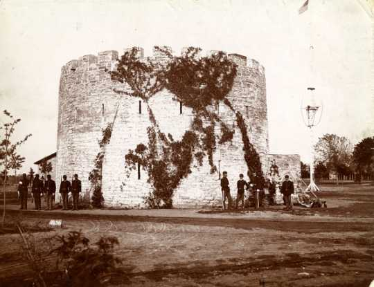 Black and white photograph of African American troops and officers of the Twenty-fifth Infantry standing by the Round Tower, c.1887.