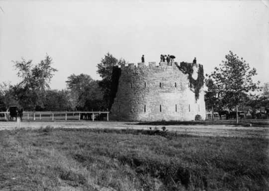 Black and white photograph of men and women with parasols standing atop the round tower, c.1900.