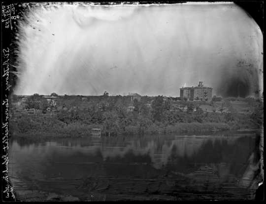 Black and white photograph of St. Anthony looking across Nicollet Island at Winslow House, right, and Universalist Church, left, ca. 1860.