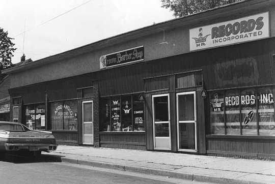 Black and white photograph of Businesses near the intersection of East 38th St and 4th Ave, Minneapolis, 1975.
