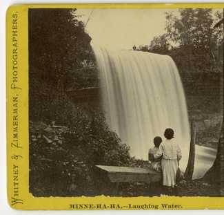 Black and white photograph of visitors below the falls, c.1869.