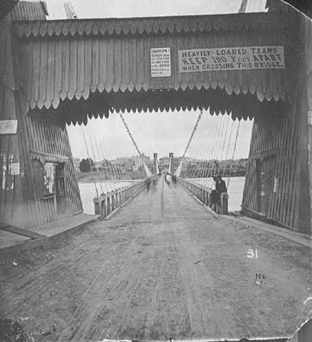 Black and white photograph of the ground level view of the Hennepin Bridge, c.1868.