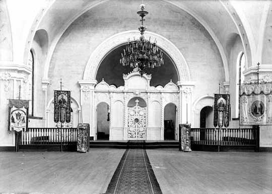 Black and white photograph of the interior of the sanctuary in St. Mary's Orthodox Cathedral, Minneapolis with an icon screen and banners, c.1906.