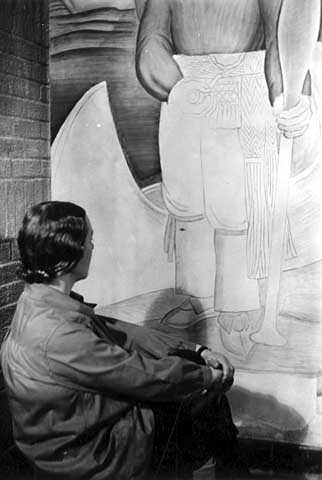 Black and white photograph of a mural in Minneapolis Armory by Elsa Jemne (seated before mural), c.1940.