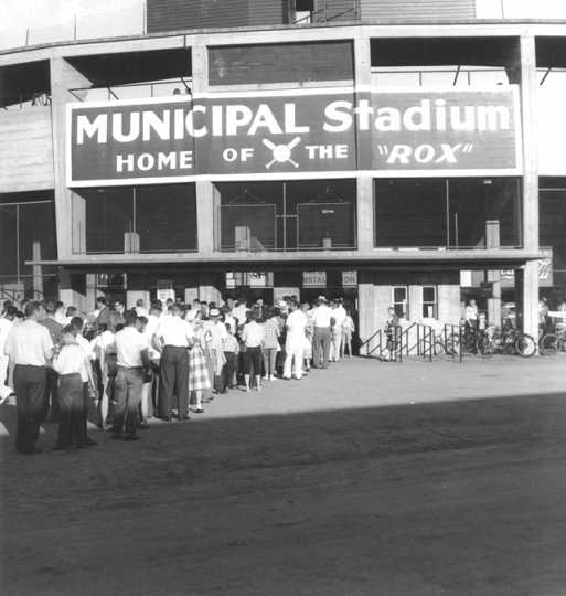 Photograph of Municipal Stadium, the home of the St. Cloud Rox from 1948-1970, showing the exterior of the stadium and a line of people waiting to get into the game, c.1950. From the Myron Hall Collection, Stearns History Museum and Research Center, St. Cloud.