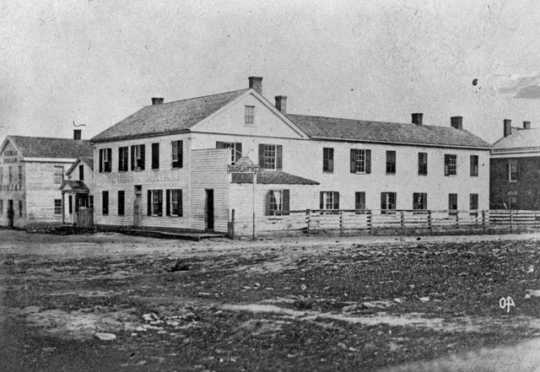 Black and white photograph of the Central House (where the Territorial Legislature met prior to the building of the State Capitol) and First State Capitol, St. Paul, ca. 1850.