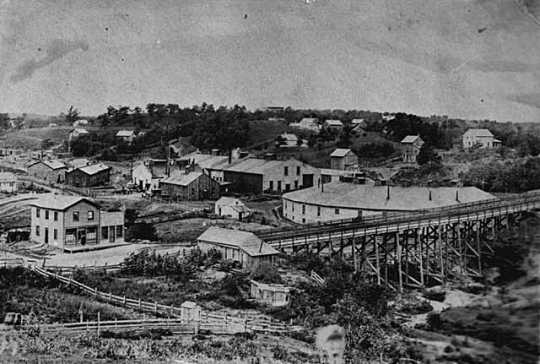 Black and white photograph of shops and roundhouse of the First Division, St. Paul and Pacific Railroad, a predecessor of Great Northern, St. Paul, 1875.