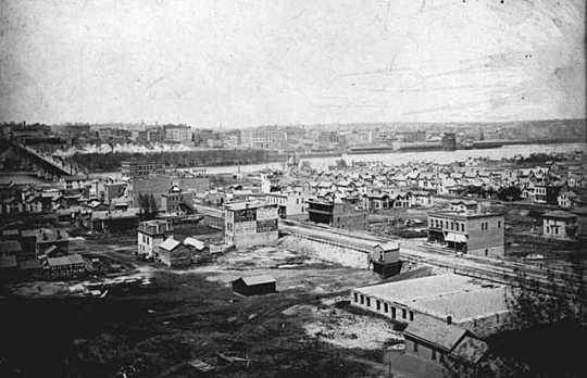Black and white photograph of the lower West Side and Wabasha Bridge, c.1885.
