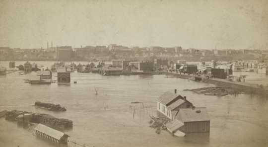 Black and white photograph looking north across the Flats during high water 1881. The raised street is Wabasha.